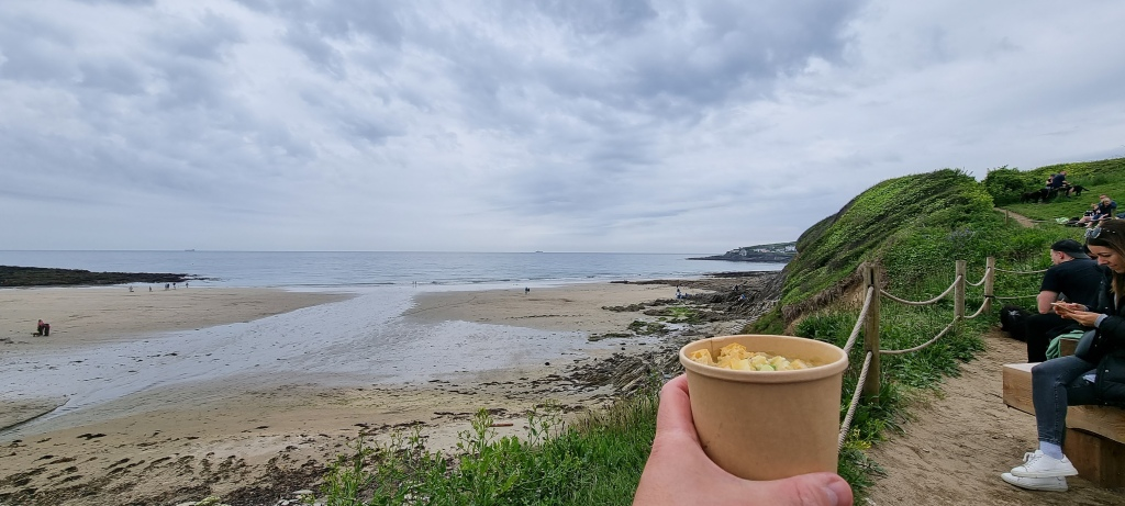 A cup of mushroom and celeriac soup with blue cheese croutons, with a view of the sea, beach and cliffs in the background.