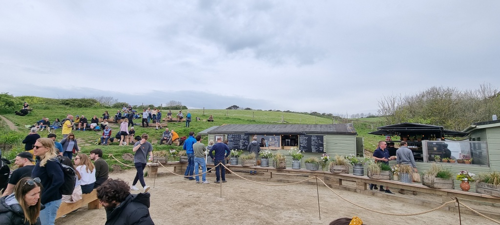 The picture shows the Hidden Hut and the seating to the front, side and behind the hut. You can see the kitchen area to the right and a wider view of the surrounding fields. There are lots of people eating or queueing.