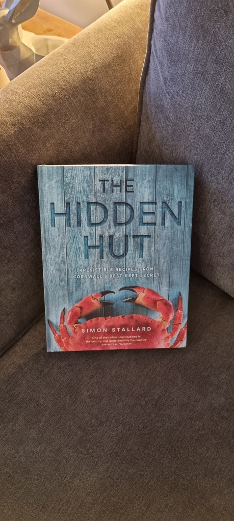 A picture of the Hidden Hut cook book on our sofa at home, ready for use. The book features countless recipes from the cafe, as well as stories of the venue. The cover features a crab claw on a blue wooden board background. The author is the Hidden Hut's owner Simon Stallard.