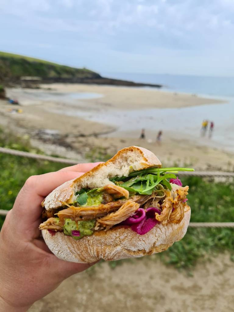 A pulled pork ciabatta, with salsa verde and salad leaves. The sandwich is pictured with the view.of the beach in the background.
